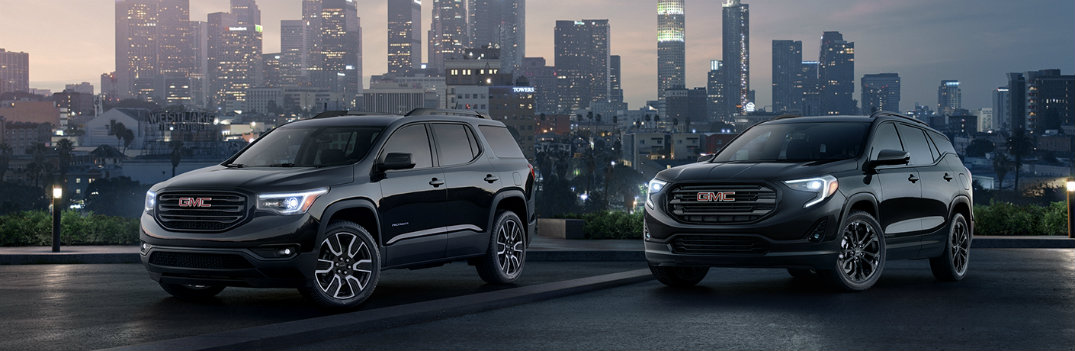 2019 GMC Terrain models exterior shot with black color paint jobs parked in a dimly lit lot outside of a city of skyscrapers lit up for the night