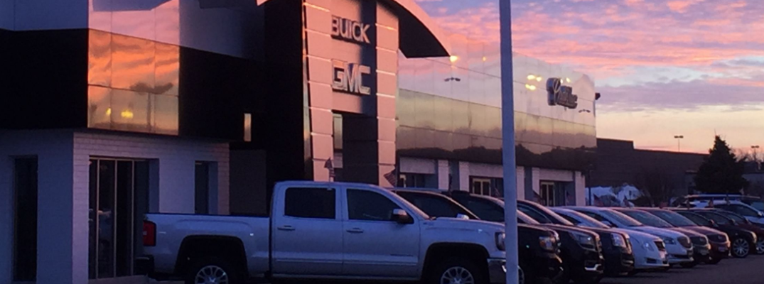 Palmen Automotive Group Palem GM dealership exterior shot of vehicles lineup at sunset