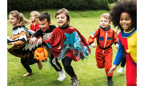 a bunch of children in halloween customes running with buckets to go trick-or-treating