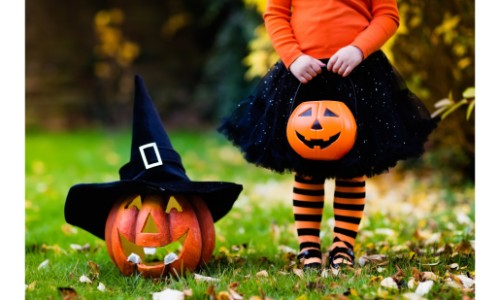 a little girl dress up in halloween colors with a trick-or-treat bucket standing by a jack-o-lantern in a witch's hat