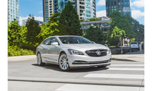 2019 Buick LaCrosse exterior shot with white silver paint color parked in a road clearing with green trees and skyscrapers behind it