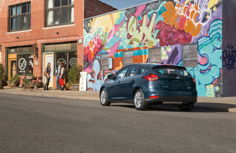 black ford focus parked in front of mural in city