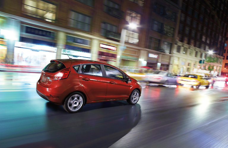 red ford fiesta driving in city at night