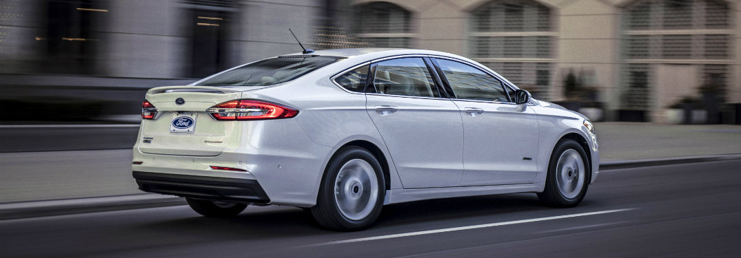 rear of white 2019 ford fusion driving in city