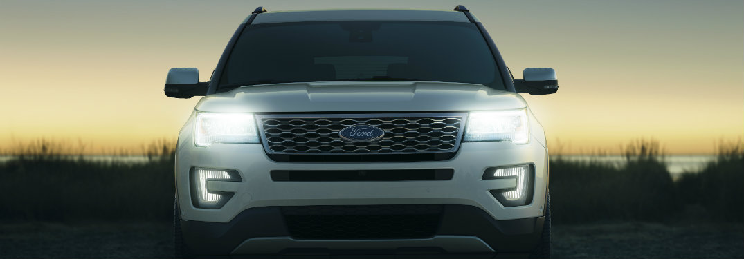 grille of white ford explorer, headlights on