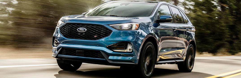 2019 Ford Edge driving down road dark paint