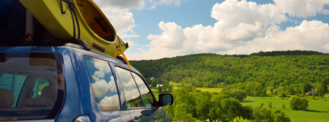 Kayak tied to the roof of a car looking towards trees