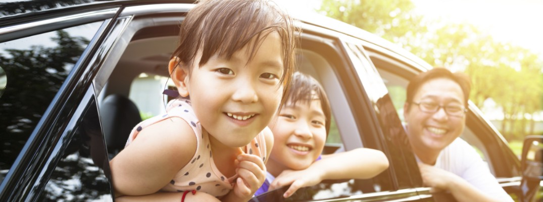 A little girl and her family sitting inside a car and smiling