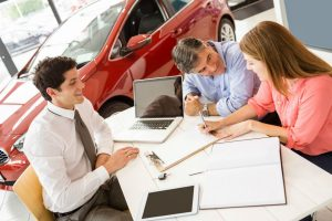 Customers Signing Paperwork for Salesman