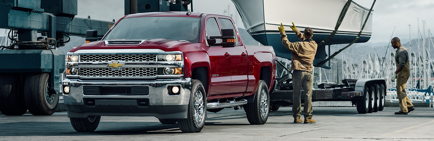 Exterior view of a red 2019 Chevrolet Silverado 1500 parked at a marina ready to tow a boat