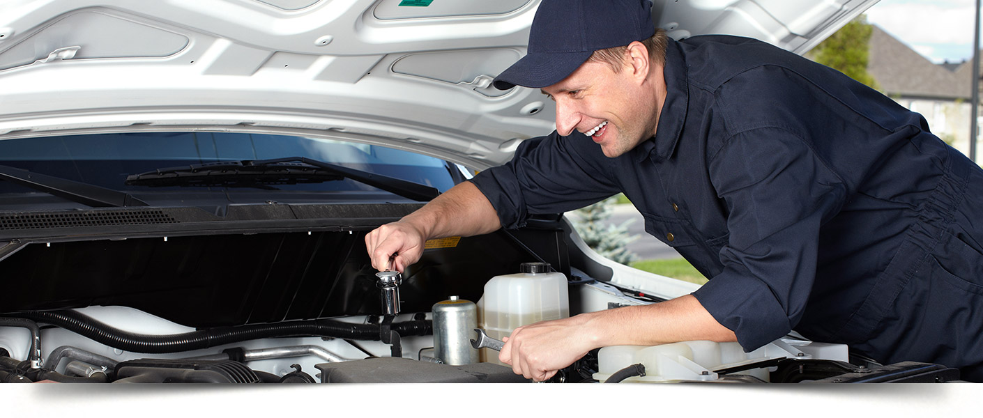 View of a service technician inspecting the engine of a vehicle