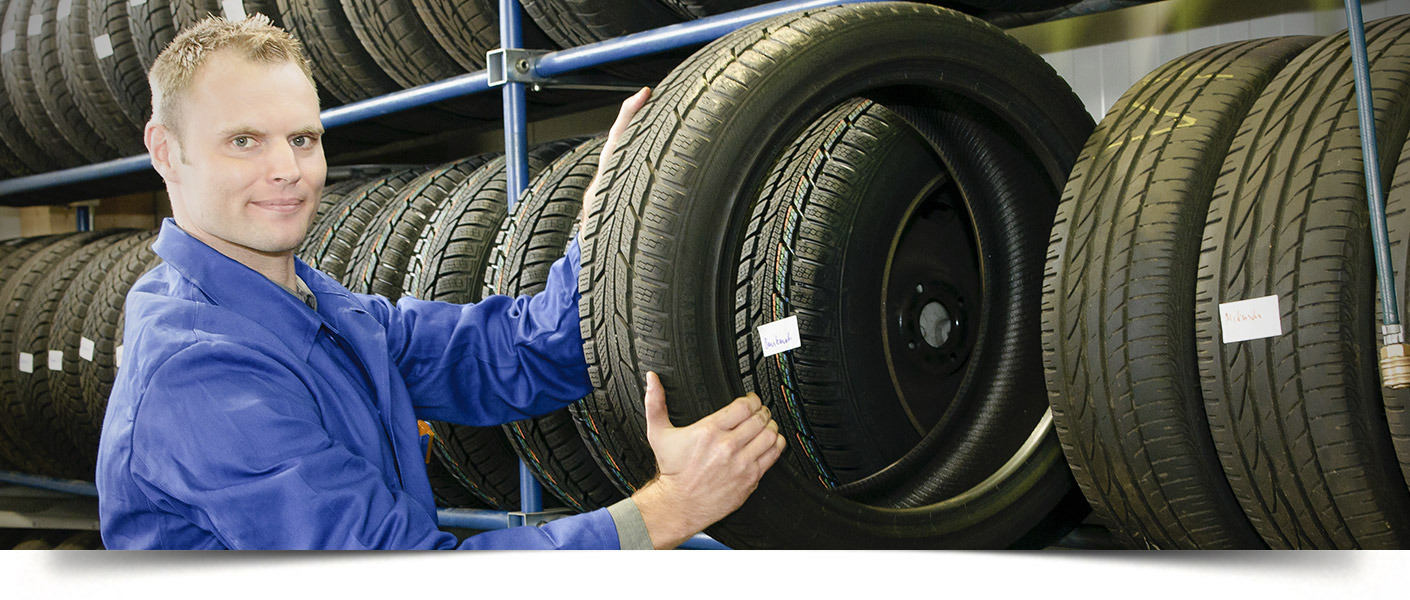 Service technician picking a new tire off the tire rack