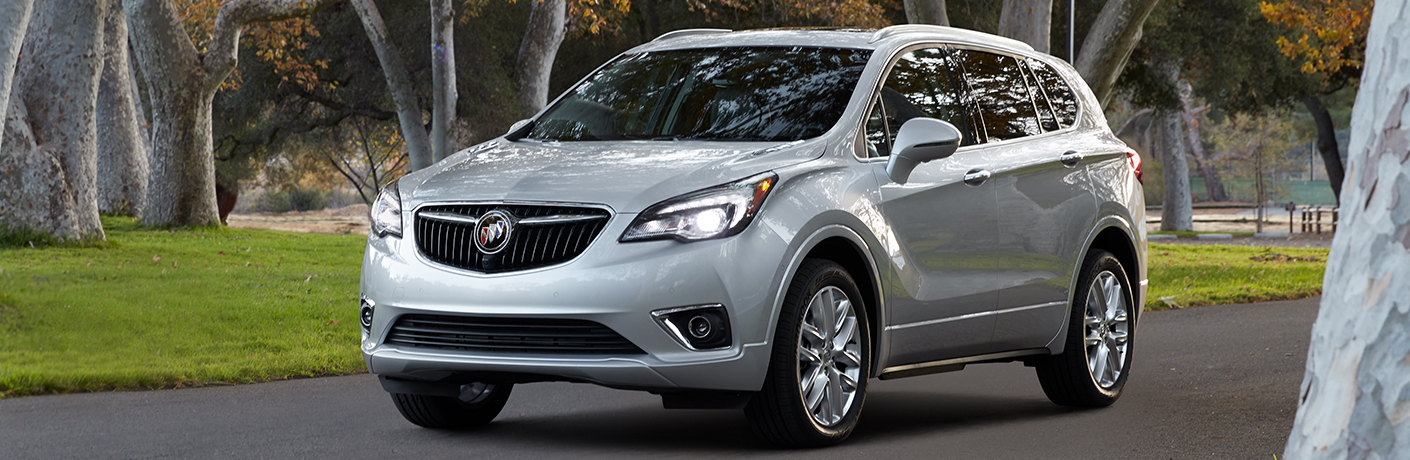 Exterior view of a silver 2019 Buick Envision driving down a suburban street