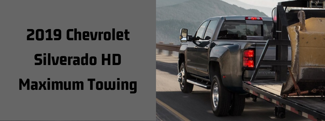 "Image of a black 2019 Chevrolet Silverado 3500HD towing a larger trailer with ""2019 Chevrolet Silverado HD Maximum Towing"" in black font"