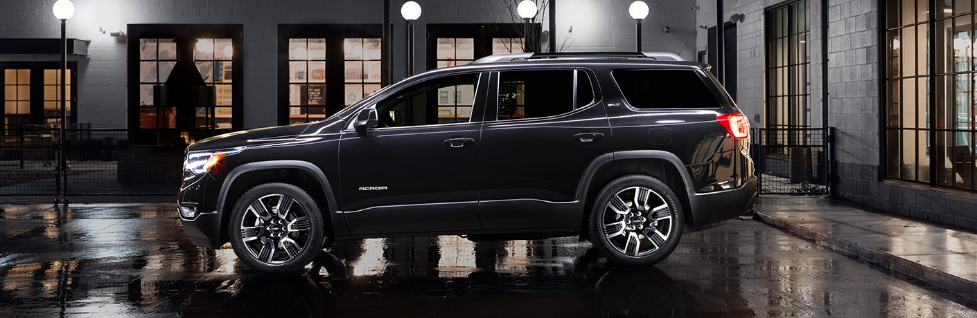 Exterior side view of a black 2019 GMC Acadia parked outside a building at night