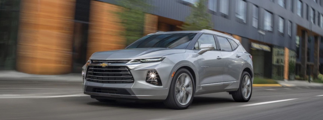 Exterior view of a silver 2019 Chevrolet Blazer driving down a city street