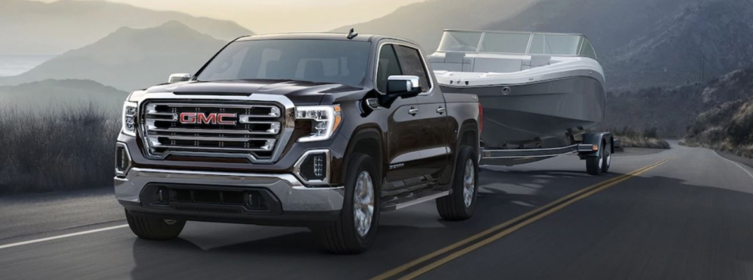 Exterior view of a black 2019 GMC Sierra towing a boat down a two-lane road