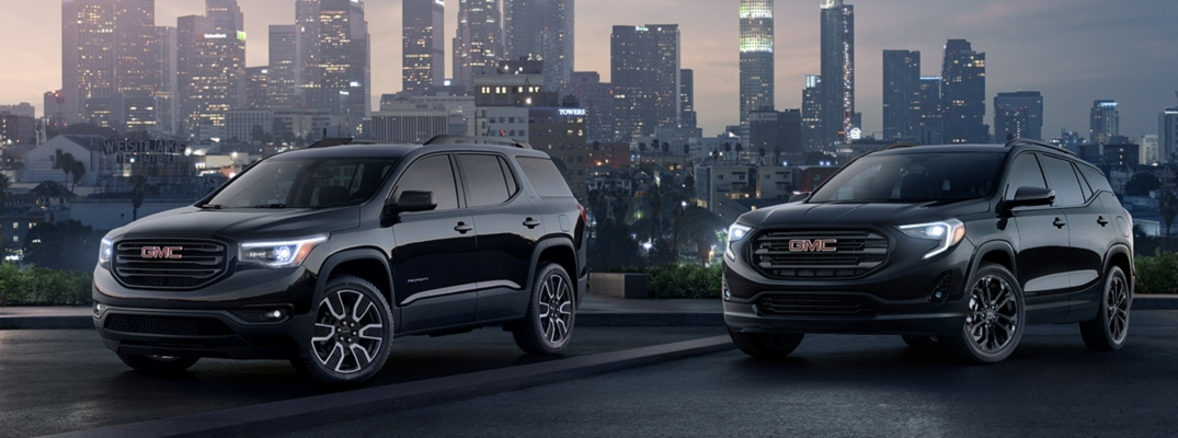 Exterior view of two black 2019 GMC Sierra models parked with skyscrapers in the background