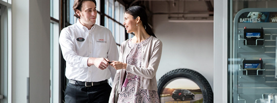 Image of a GM Certified Service Technician speaking with a customer about her maintenance services