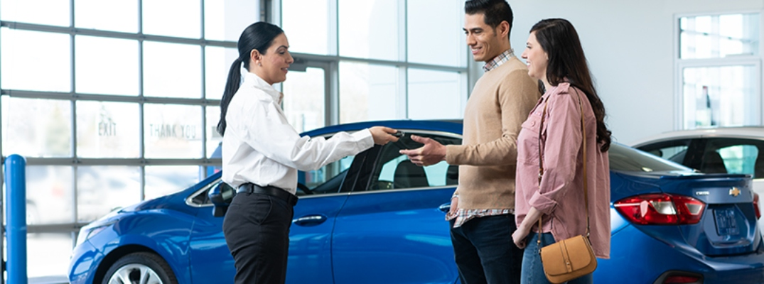 Image of a GM salesperson handing the keys to a Certified Pre-Owned GM vehicle to a man and a woman