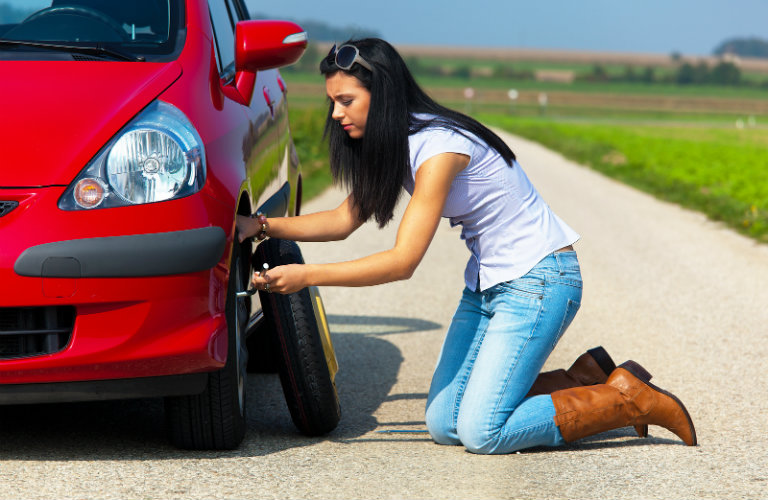 woman changing a tire on red car