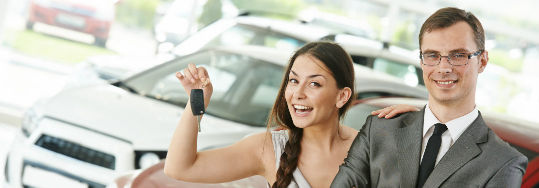 man smiling, woman holding key to new car