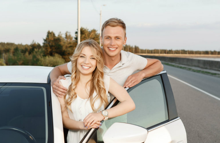 young couple standing by white car