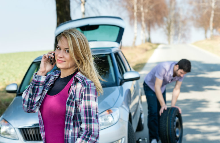 man changing tire while woman talks on phone