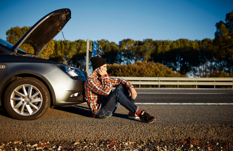 man sitting by broken down car calling someone on phone