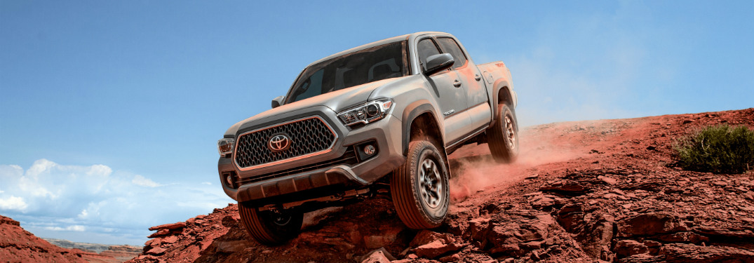 toyota tacoma driving over a rocky hill