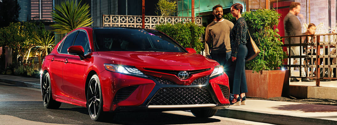 red 2019 camry with people standing next to it