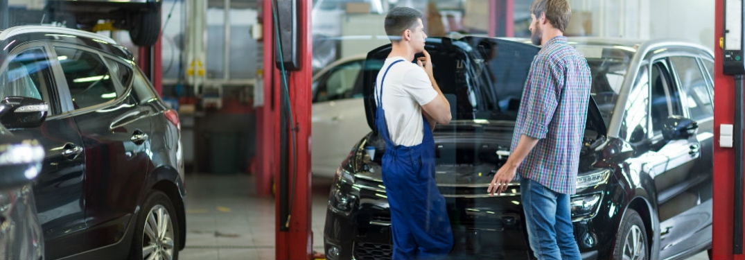 man talking to mechanic in shop