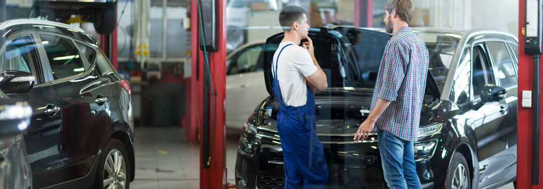 man and service technician discuss car.