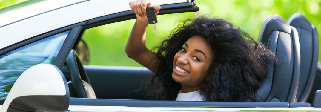 Teen driver smiles with car keys in hand