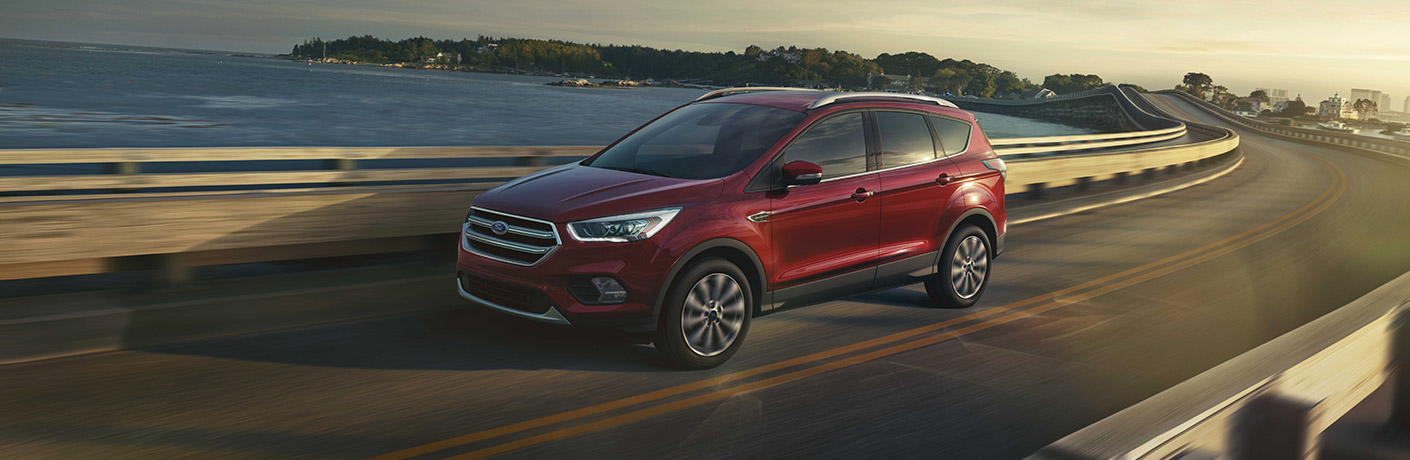 Exterior view of a red 2018 Ford Escape driving over a bridge with water in the background