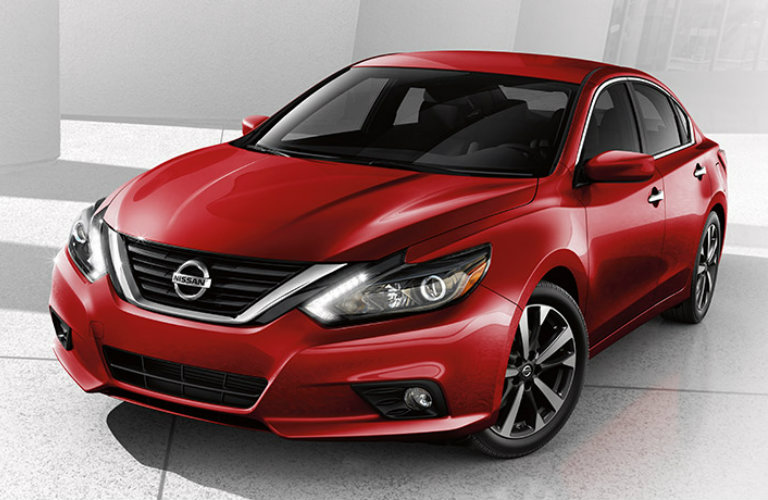 Exterior view of a red 2017 Nissan Altima parked in a white showroom