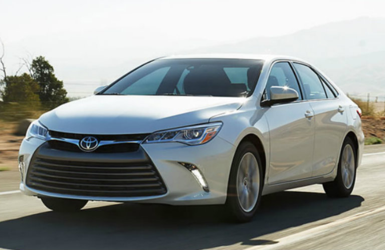 Exterior view of a silver 2017 Toyota Camry driving down an empty two-lane road