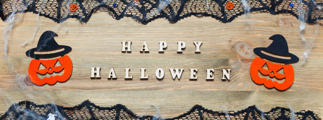 Happy Halloween text with pumpkins to the left and right surrounded by black cobwebs
