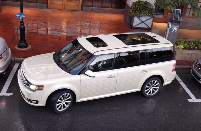 Exterior view of a white 2013 Ford Flex parallel parking in the city