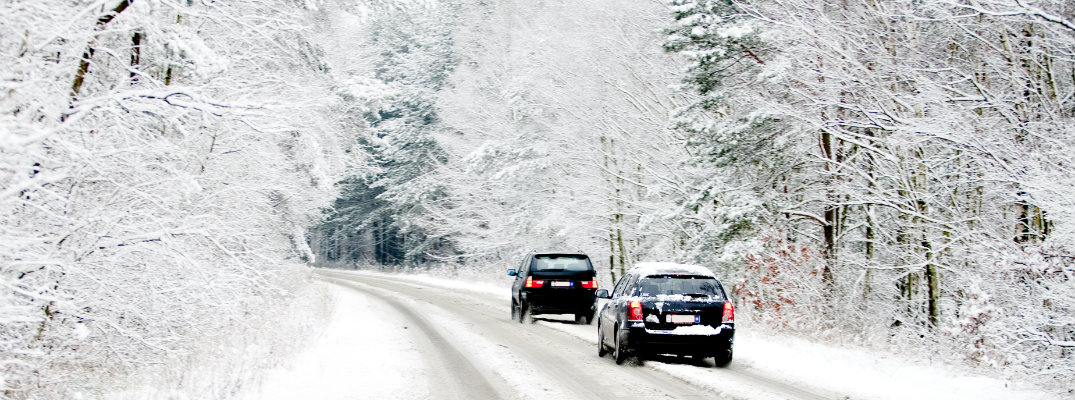 View of two cars traveling on snowy road during the winter