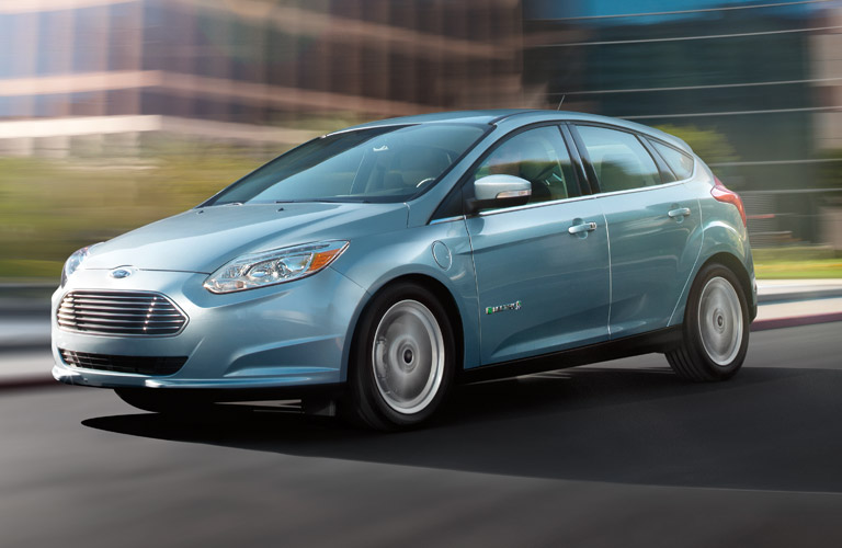 Exterior view of a light blue 2013 Ford Focus driving down a city street