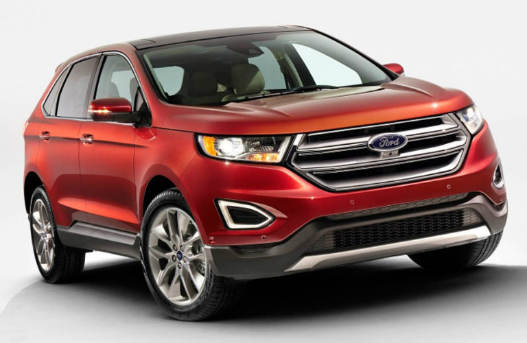 Exterior view of a red 2015 Ford Edge parked in a white showroom