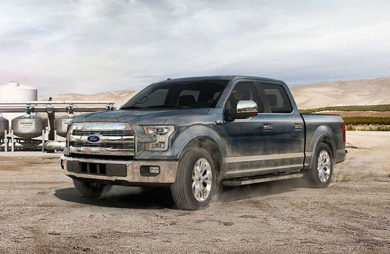 Exterior view of a gray 2015 Ford F-150 parked on dirt job site