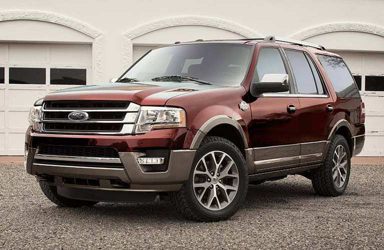 Exterior view of a maroon 2016 Ford Expedition parked in a driveway outside a 3-car garage