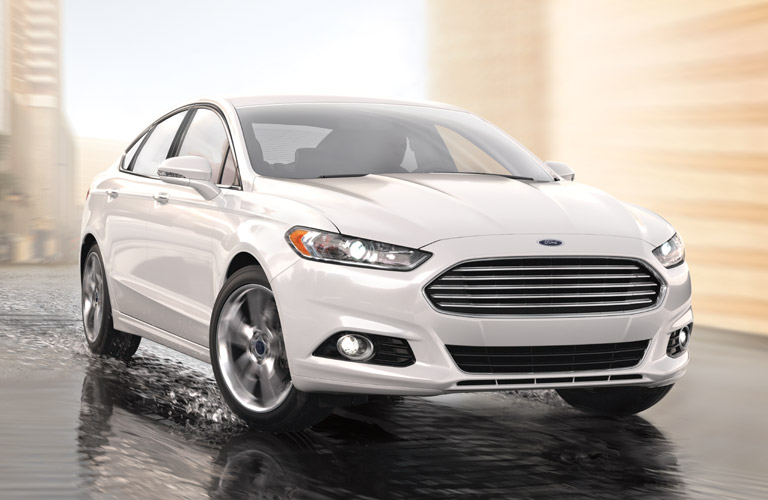 Exterior view of a white 2016 Ford Fusion driving on wet concrete