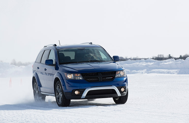 Exterior view of a blue 2017 Dodge Journey driving on snow-covered terrain