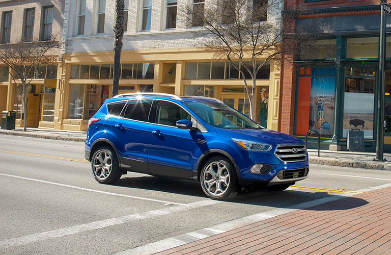 Exterior view of a blue 2017 Ford Escape driving down a city street