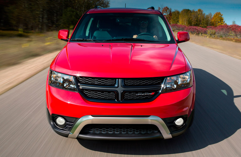 Exterior view of the front of a 2014 Dodge Journey driving down a country road