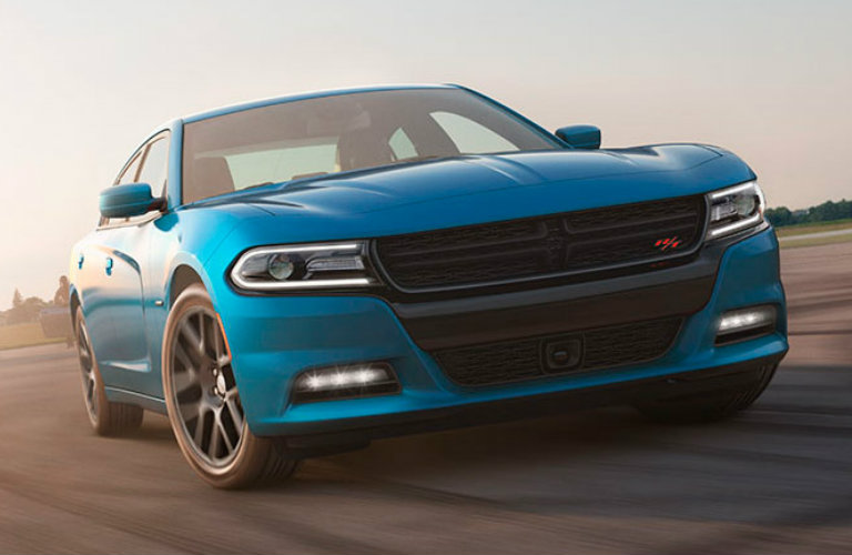 Exterior view of a light-blue 2015 Dodge Charger driving around a race track