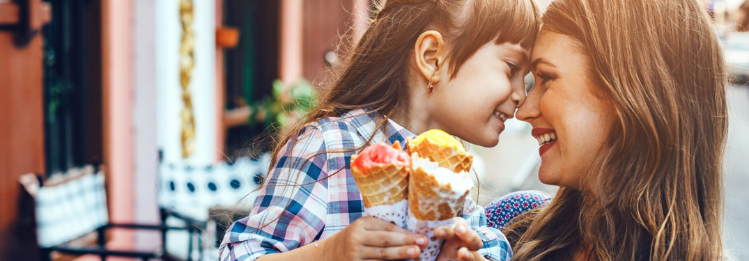 Image of a mother and daughter pushing their noses against each other while holding their ice cream cones against each other's cone as well